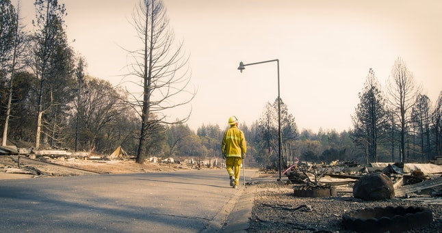 Alone on an empty street, one firefighter surveys the damage in a neighborhood where every home burned. Remnants of building materials, boulders, and rubble is visible everywhere beneath the smoky sky. Above the firefighter, a single streetlight remains standing. There's some barely visible red danger tape and many standing burned trees. Ash and charcoal everywhere.