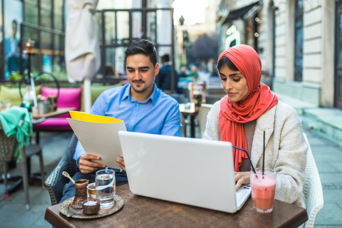 Business A Muslim woman and a man are talking and working together in a restaurant. Young businesswoman and man working together on a laptop, and having a business conversation at a cafe