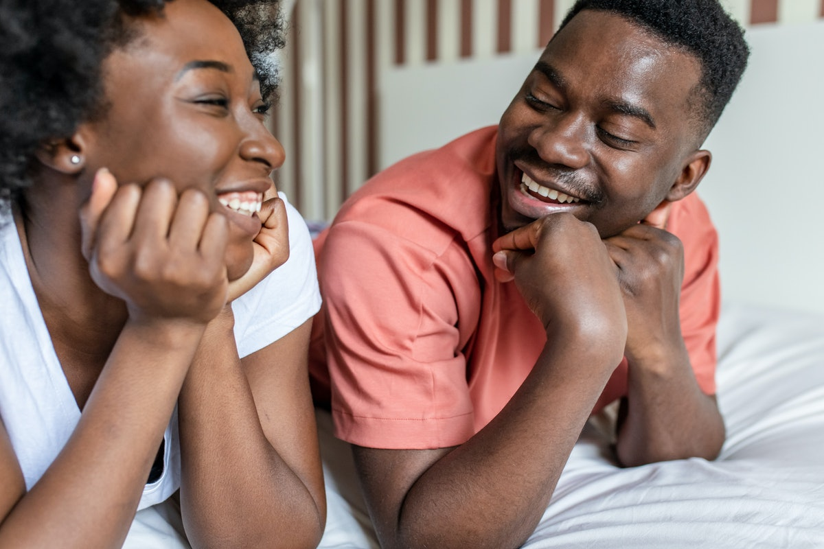 Young couple laying in bed in the morning and smiling