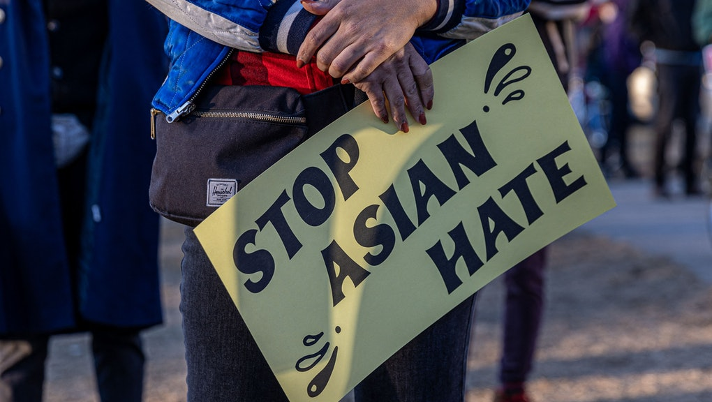 """A person holds a sign during the """"Asian Solidarity March"""" rally against anti-Asian hate in response to recent anti-Asian crime on March 18, 2021 in Minneapolis, Minnesota. - The shooting rampage in Atlanta by a 21-year-old white man that left six women of Asian origin dead has laid bare the fears of an Asian-American community on edge over a spike in hate crimes because of the coronavirus pandemic. (Photo by Kerem Yucel / AFP) (Photo by KEREM YUCEL/AFP via Getty Images)"""