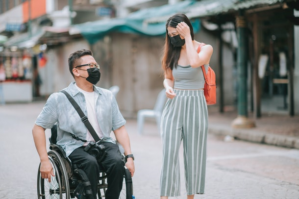 asian chinese male with disability on wheelchair crossing road with his friends in kuala lumpur