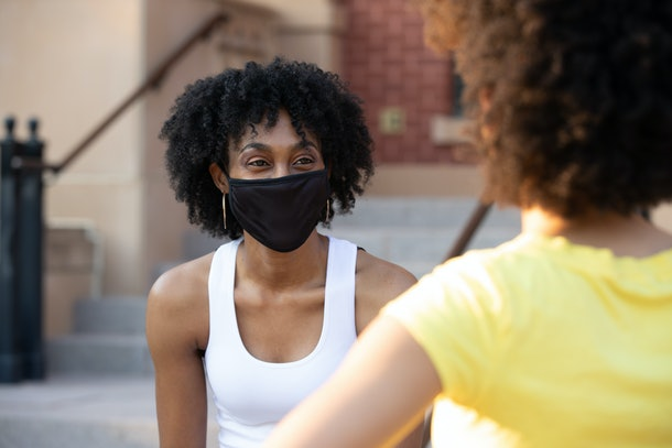 Young adult woman sitting on steps and wearing a mask while talking to friend