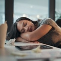 Shot of a young businesswoman lying with her head down on a desk in an office at night