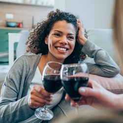 Shot of two happy women sitting on the floor making small talk and drinking wine. Smiling friends toasting with red wine at home. Two female friends relaxing at home with glass of wine.