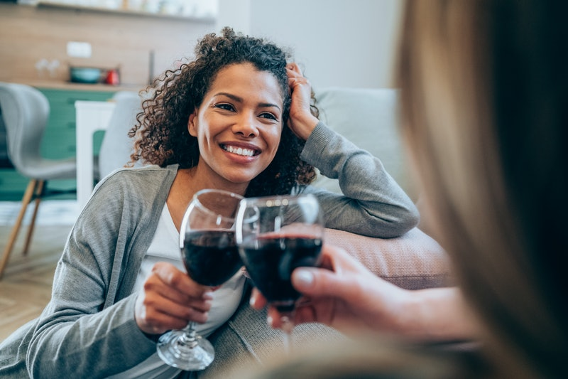 Shot of two happy women sitting on the floor making small talk and drinking wine. Smiling friends to...
