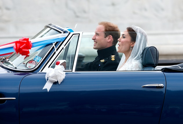 LONDON, UNITED KINGDOM - APRIL 29: (EMBARGOED FOR PUBLICATION IN UK NEWSPAPERS UNTIL 24 HOURS AFTER CREATE DATE AND TIME) Prince William, Duke of Cambridge and Catherine, Duchess of Cambridge leave Buckingham Palace on route to Clarence House, driving Prince Charles, Prince of Wales's 1969 Aston Martin DB6 Volante decorated with L plates, bunting, ribbons and balloons, following their wedding reception on April 29, 2020 in London, England. The marriage of Prince William, the second in line to the British throne to Catherine Middleton was led by the Archbishop of Canterbury and was attended by 1900 guests, including foreign Royal family members and heads of state. Thousands of well-wishers from around the world have also flocked to London to witness the spectacle and pageantry of the Royal Wedding. (Photo by Max Mumby/Indigo/Getty Images)