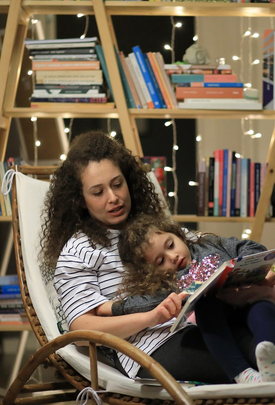 Curly mother and curly daughter reading a book lying on the reading chair in front of the library