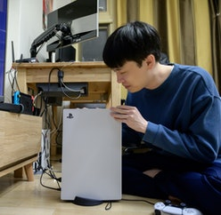 In a photo taken on November 12, 2020, a gamer sets up the new Sony Playstation PS5 at his home in Seoul after Sony launched the new console in select markets around the world. (Photo by Yelim LEE / AFP) (Photo by YELIM LEE/AFP via Getty Images)