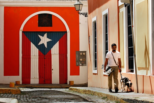 SAN JUAN, PUERTO RICO - OCTOBER 2: Celso Melendez, age 25, and his dog Popeye live in Old San Juan, where Celso works as a bartender and studies chemical engineering. Celso feels it will be even harder for Puerto Rico to get statehood after the hurricane with all of the debt the island has taken on The debate over whether or not Puerto Rico should be given statehood has surfaced again with the attention hurricane Maria brought to the island. (Photo by Carolyn Cole/Los Angeles Times via Getty Images)