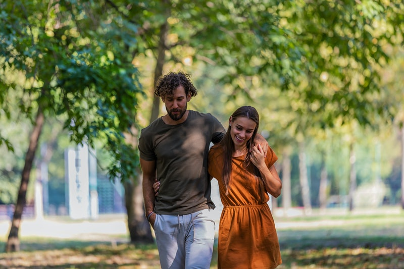 Portrait of Cheerful Young Couple who is Hugging Each Other in the Park Path and Having a Nice Conversation and Sweet Emotions.