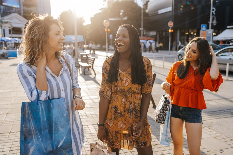 Three cheerful young female friends enjoying sunny day in the city , having fun together after successful shopping