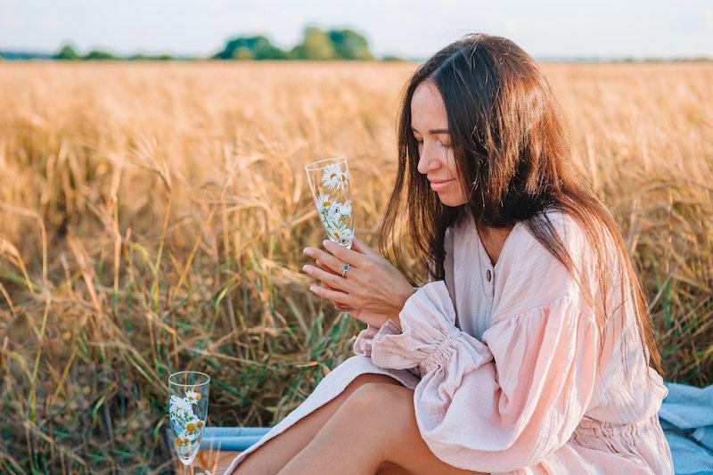 Beautiful woman in wheat field on picnic.
