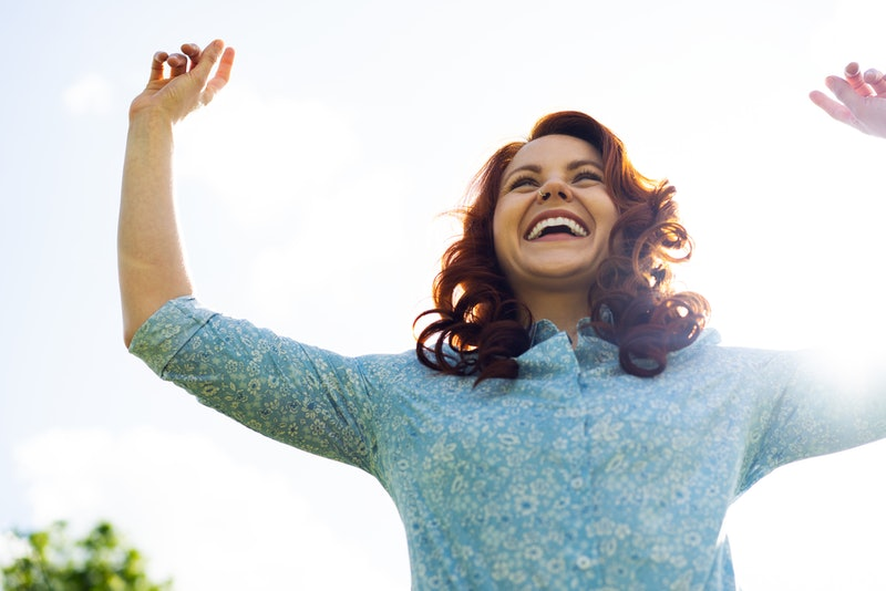 Woman jumping in air with her arms up whilst smiling