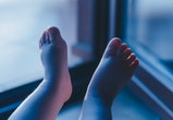 Boy's feet illuminated by light comming from balcony