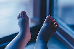 Boy's feet illuminated by light comming from balcony