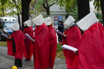 """Woman's right activists wearing protective face masks are dressed as the Handmaids from the dystopian novel The Handmaid's Tale from the Canadian author Margaret Atwood perform during a protest against tightening of abortion law on October 21, 2020 in Warsaw, Poland. A dozen of Woman's rights activists gathered in front of the Constitutional Tribunal the day prior the hearing of the Polish Constitutional Tribunal as the court prepares to issue a decision regarding the constitutionality of access to abortion on the ground of """"severe and irreversible foetal defect or incurable illness that threatens the foetus life"""". (Photo by Aleksander Kalka/NurPhoto via Getty Images)"""