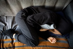 High angle shot of a woman experiencing stomach pain and holding a hot water bottle lying on the sofa