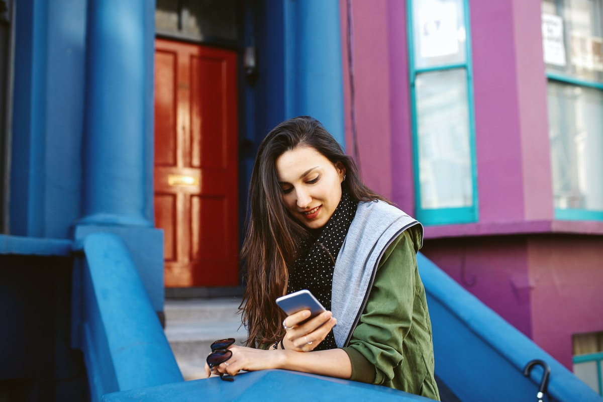 Vintage toned portrait of a young beautiful brunette woman in London, near Notting Hill. She is wearing casual Autumn clothes, an olive green parka jacket, orange knitted sweater and skinny black jeans, sitting by her apartment door, waiting for a friend, texting on the cellphone.