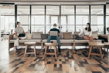 Businesspeople working and maintaining social distance on a sofa in a modern office