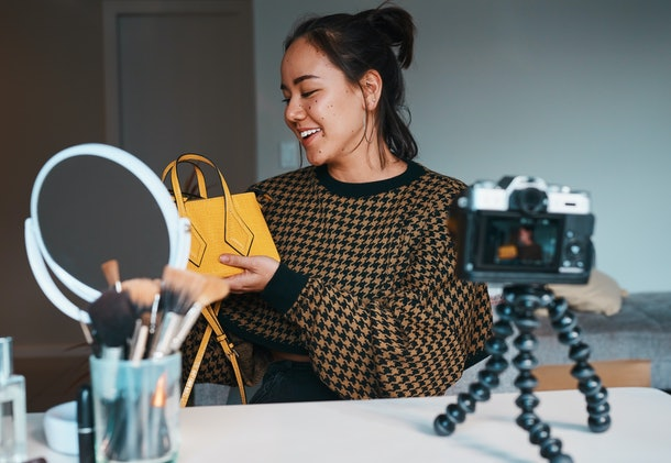 Shot of a young woman showing off a stylish bag while filming a fashion blog at home