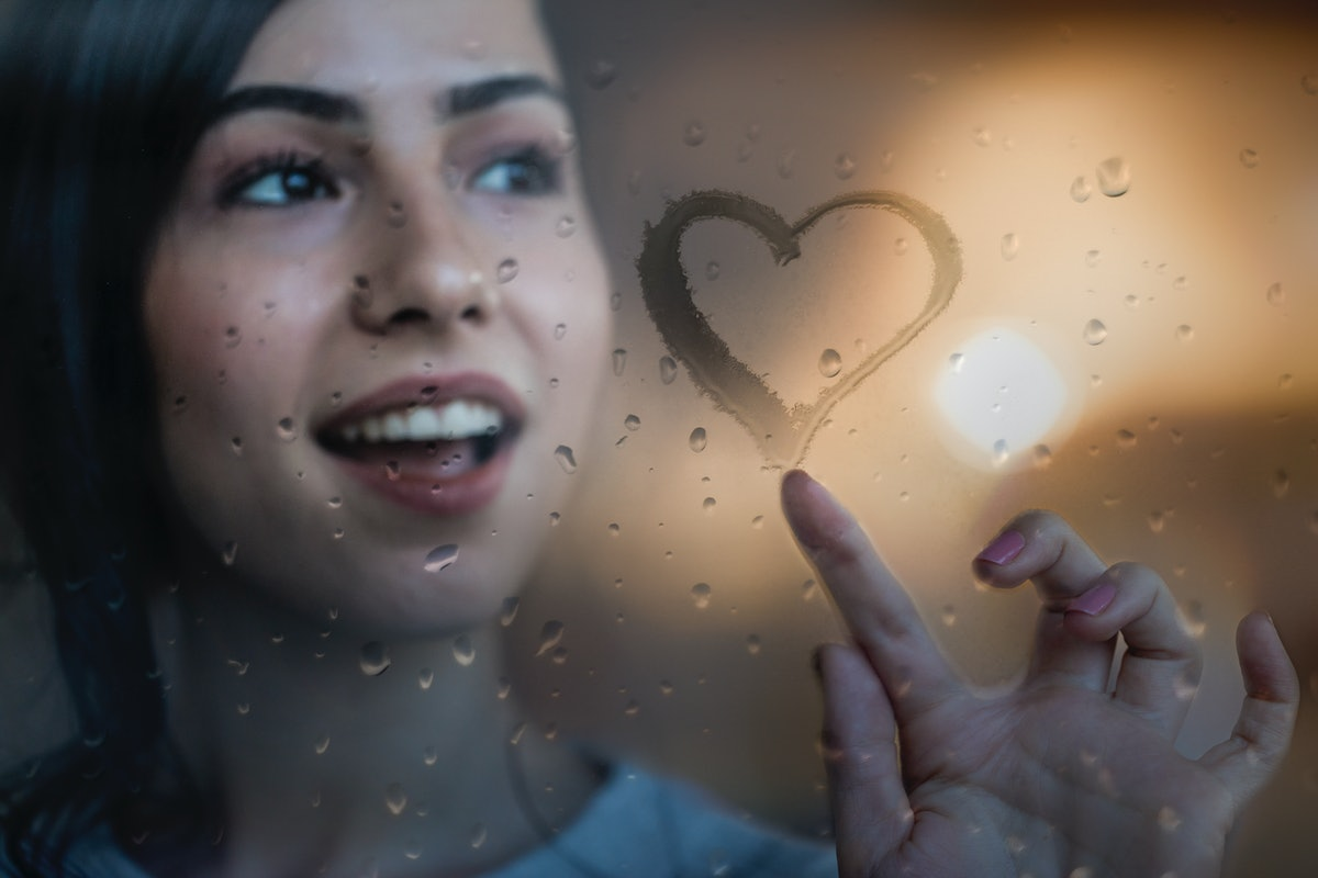 Young woman drawing heart on a foggy window