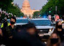 WASHINGTON, DC - APRIL 23: Police cars follow behind demonstrators during a protest on April 23, 202...
