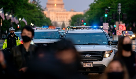 WASHINGTON, DC - APRIL 23: Police cars follow behind demonstrators during a protest on April 23, 2021 in Washington, DC. Activists with the group Freedom Fighters DC gathered on Friday for the first of three days worth of rallies calling to abolish the police. (Photo by Stefani Reynolds/Getty Images)