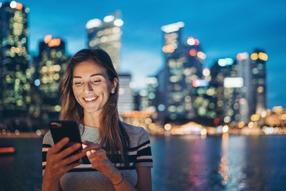Portrait of a smiling young woman holding a cell phone outdoors in the city
