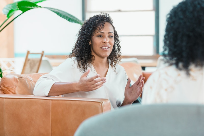 A mid adult woman gestures during a counseling session with an unrecognizable mental health professional.