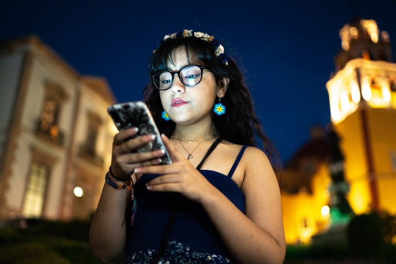 A woman looks at her phone while walking outside at night. How to ghost someone in the nicest way possible.