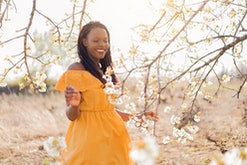 Young African woman enjoying her pregnancy at the orchard in bloom.