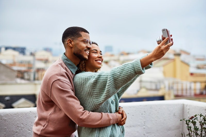 Smiling young woman taking selfie with boyfriend at building terrace. Happy couple is enjoying while making memories. They are spending leisure time at rooftop.