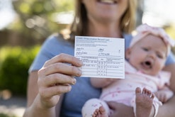 A mother with a proof of Vaccination card and her new born baby girl.