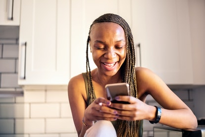 Happy young African woman sitting in her kitchen while texting on smart phone and smiling