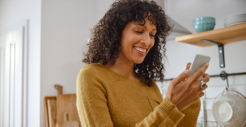 Happy young woman using her smartphone while standing in kitchen. Here's how to hide your likes on Instagram.