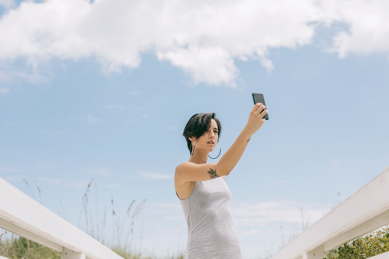 Young woman taking a self portrait at the beach. Apple's new privacy feature in iOS 14.5 lets you stop apps from tracking your data.