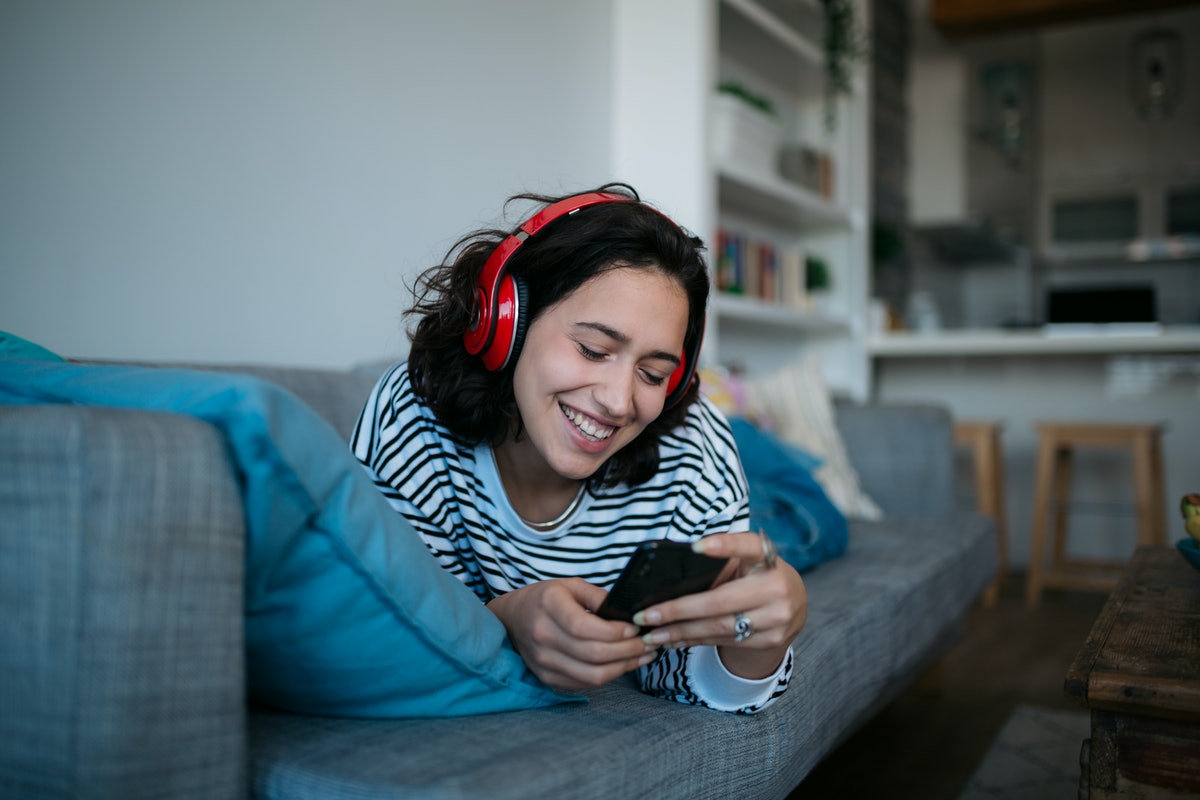 Happy Caucasian woman relaxing at home, smiling and listening to music using headphones and a smart phone