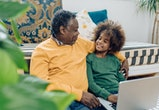 African American teenage girl enjoying at home with grandpa and using a laptop.