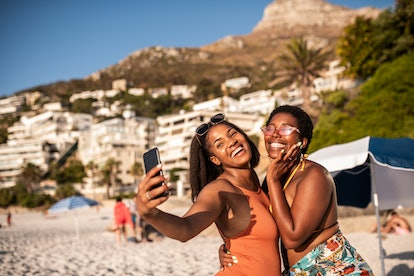 Two young smiling African females making a selfie at the beach
