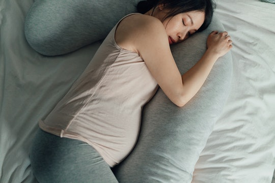 Elevated view of Asian Pregnant woman resting in bed. Comfortable sleeping positions during pregnancy. Tiredness and sleep problems during pregnancy.