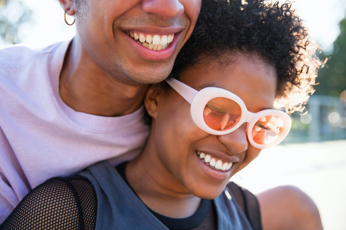 A close up of a fashionable young African American couple leaning on each other and smiling outdoors