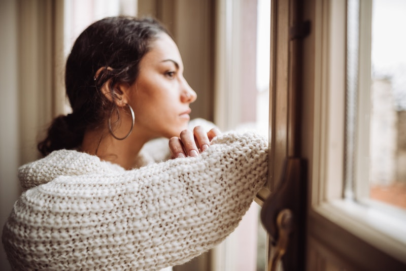 A woman in a knit sweater thinks about her mom on Mother's day. Here's how to observe mother's day when your mom has passed away.