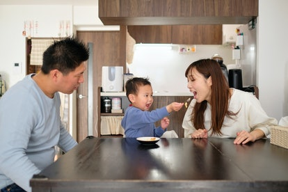 Child feeding sweet food to parents at home