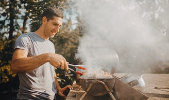 Handsome man preparing meat on old fashioned brick barbecue