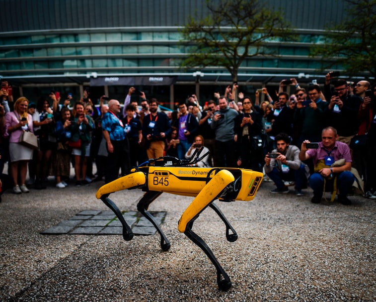 """People take pictures and videos of Boston Dynamics Robot Dog named """"Spot"""" during a presentation on the last day of the Web Summit in Lisbon on November 7, 2019. - Europe's largest tech event Web Summit is held at Parque das Nacoes in Lisbon from November 4 to November 7. (Photo by PATRICIA DE MELO MOREIRA / AFP) (Photo by PATRICIA DE MELO MOREIRA/AFP /AFP via Getty Images)"""