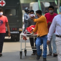 Family members bring a relative suffering from the Covid-19 coronavirus to a hospital for in Allahab...