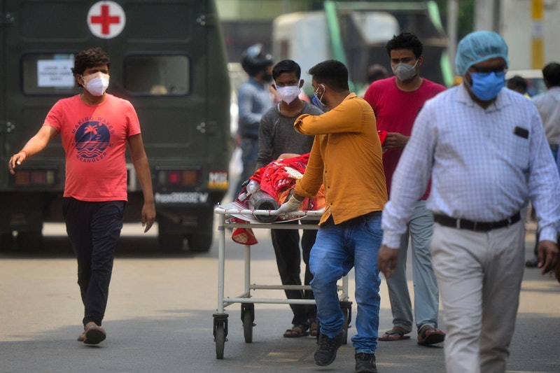 Family members bring a relative suffering from the Covid-19 coronavirus to a hospital for in Allahabad on April 29, 2021. (Photo by SANJAY KANOJIA / AFP) (Photo by SANJAY KANOJIA/AFP via Getty Images)
