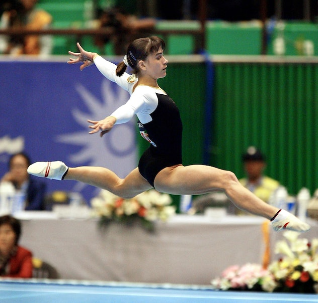 Oksana Chusovitina of Uzbekistan performs on the floor during the women's apparatus finals for the 14th Asian Games in Busan, 05 October 2002.  Chusovitina finished in first place to grab gold together with Zhang Nan from China.    AFP PHOTO/YOSHIKAZU TSUNO (Photo by YOSHIKAZU TSUNO / AFP)        (Photo credit should read YOSHIKAZU TSUNO/AFP via Getty Images)