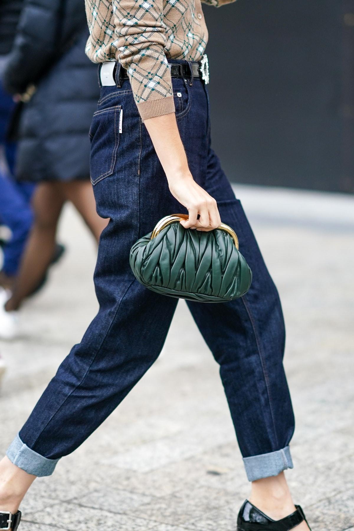 PARIS, FRANCE - OCTOBER 06: A guest wears a green woven leather Miu Miu bag, blue hem jeans, outside...