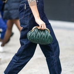 PARIS, FRANCE - OCTOBER 06: A guest wears a green woven leather Miu Miu bag, blue hem jeans, outside Miu Miu, during Paris Fashion Week - Womenswear Spring Summer 2021, on October 06, 2020 in Paris, France. (Photo by Edward Berthelot/Getty Images)